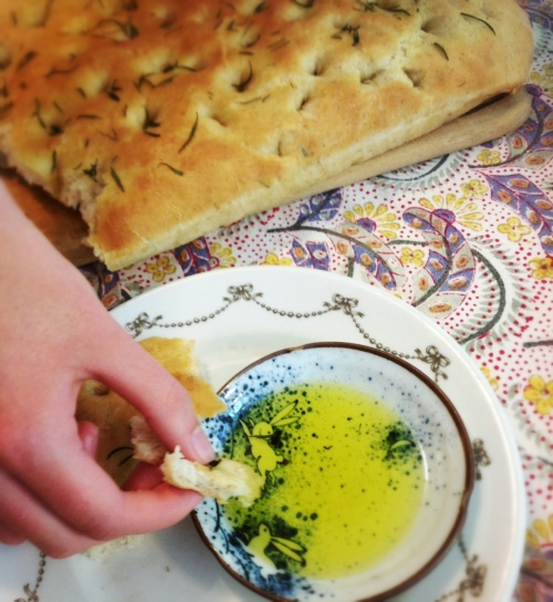 dipping focaccia in extra virgin olive oil